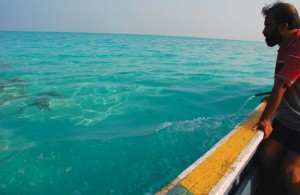 A fisherman soaking in the vast blue-green expanse from his boat