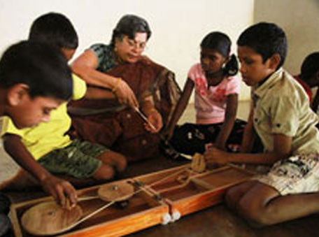 The writer (centre) training children in spinning the charkha