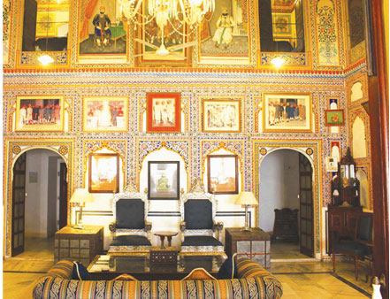 The Durbar hall of Castle Mandawa, now being used as a visitor's lounge in the hotel section of the castle. Much of the painting has been restored and the seating apart from the throne chairs, are modern