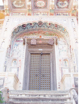 The covered entrance of the Chokhani haveli with ornate arch and overhang, above the intricately carved doorway