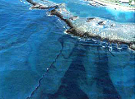 An oil slick moving onto coral reefs at Galeta at low tide after the Bahia las Minas refinery spill, Panama, April 1986